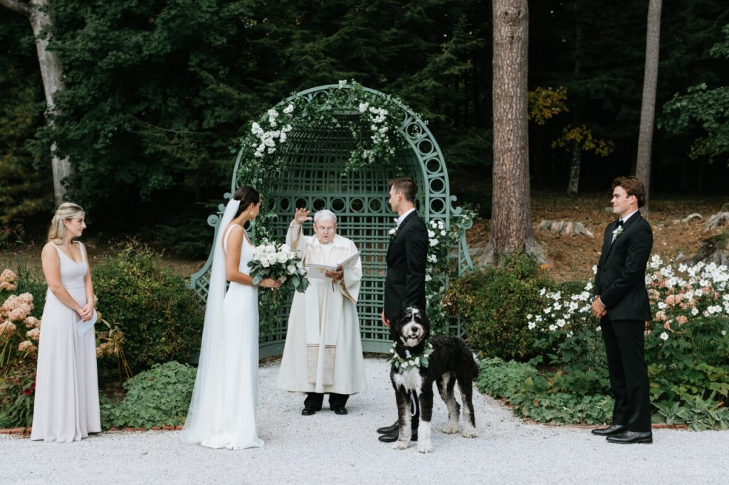 Close up of a bride and groom getting married in The French Garden with their dog by their side.