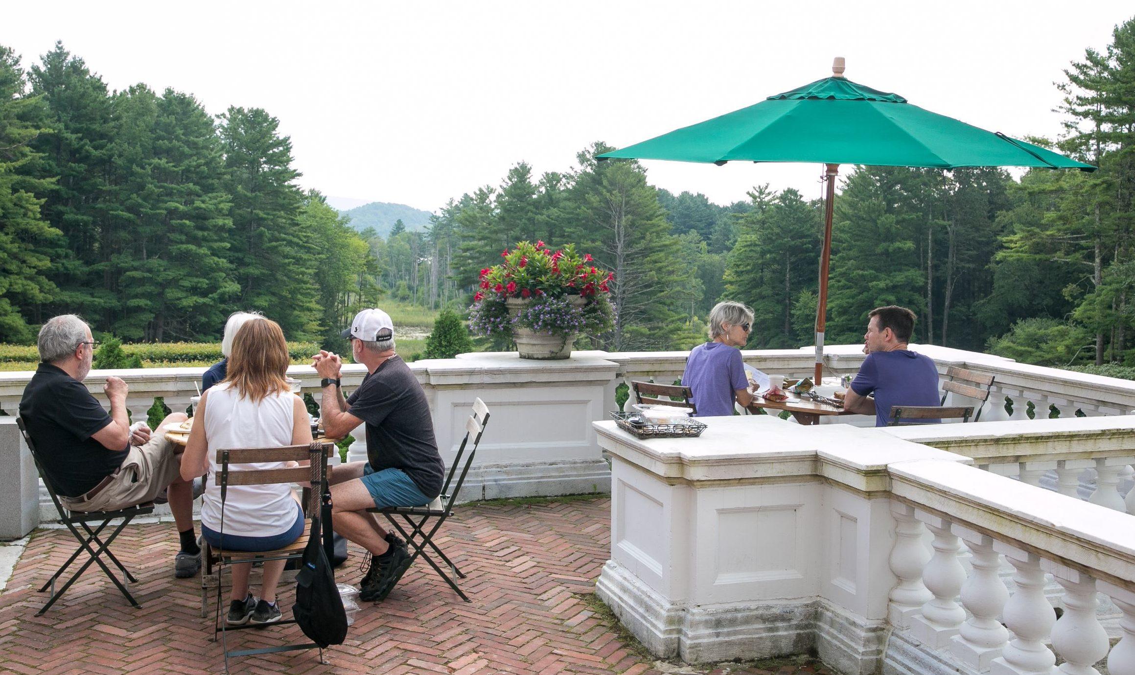 Visitors enjoying lunch under an umbrella at The Terrace Café.